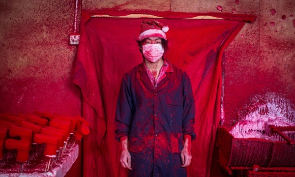 Mandatory Credit: Photo by Imaginechina/REX (4301626b) 19-year-old worker Wei wearing a face mask and a Christmas hat covered in red powder Christmas decorations being made at a factory in Yiwu city, Zhejiang province, China - 15 Dec 2014 The city of Yiwu is known as China?s massive Christmas market. From 2001 till now, the booming Christmas production industry there has grown from a mere 10 factories to more than 600. The village produces 60 percent of the world's Christmas decorations. 19-year-old factory worker Wei says he knows that Christmas is a festival, but doesn't really know what it's about. Wei and his parents came to Yiwu from their home province after their friends told them that they could make up to 4,000 RMB a month working in the factories. Wei and his father spend 10 hours in this factory every day producing plastic snowflakes for about 3,000 RMB per month. Red powder used as colouring hovers in the air, and the two get through about 10 face masks a da. Although he wears a Christmas hat at work, Wei?s father doesn't intend on celebrating the holiday. The hat protects his hair from the red dust which covers them from head to toe like soot after several hours of work.